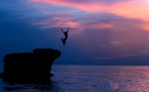 Brave girl jumping from the rocks in the evening on beautiful pu